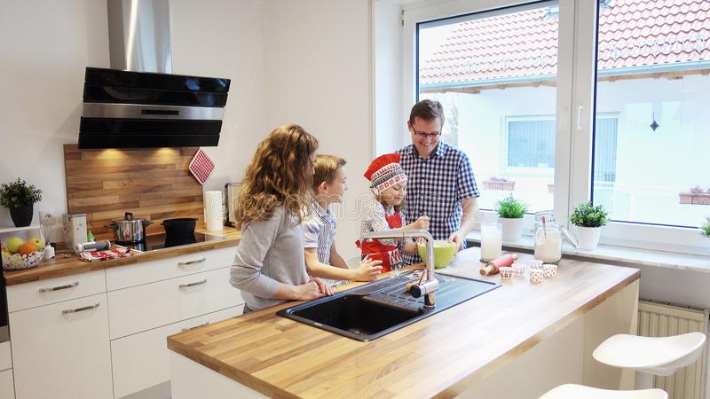 Happy young family cooking and having fun in the morning at kitchen. Happy young family cooking and having fun in the morning at modern kitchen royalty free stock images