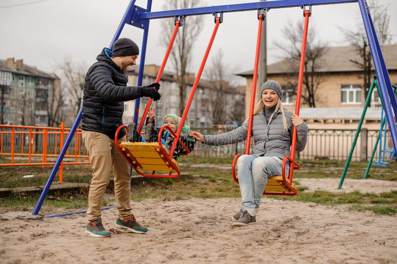 Happy young family couple on a swing with a little son royalty free stock photography