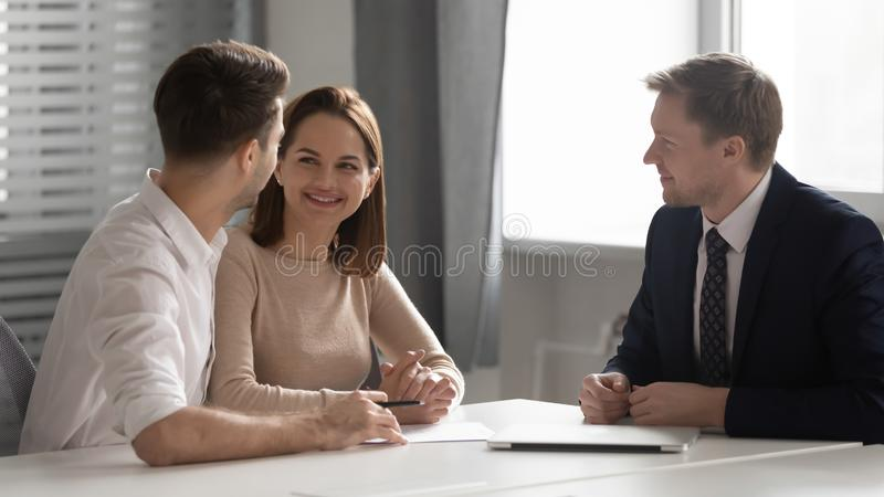Happy young family couple making decision meeting bank manager insurer. Happy young couple making decision meeting bank manager insurer, male realtor broker stock photo