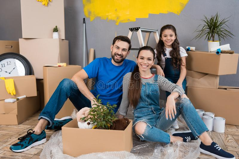 Happy young family dismantles cardboard boxes and makes repairs in new house. stock images