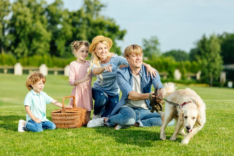 Happy young family with dog resting on green grass. At picnic stock photo