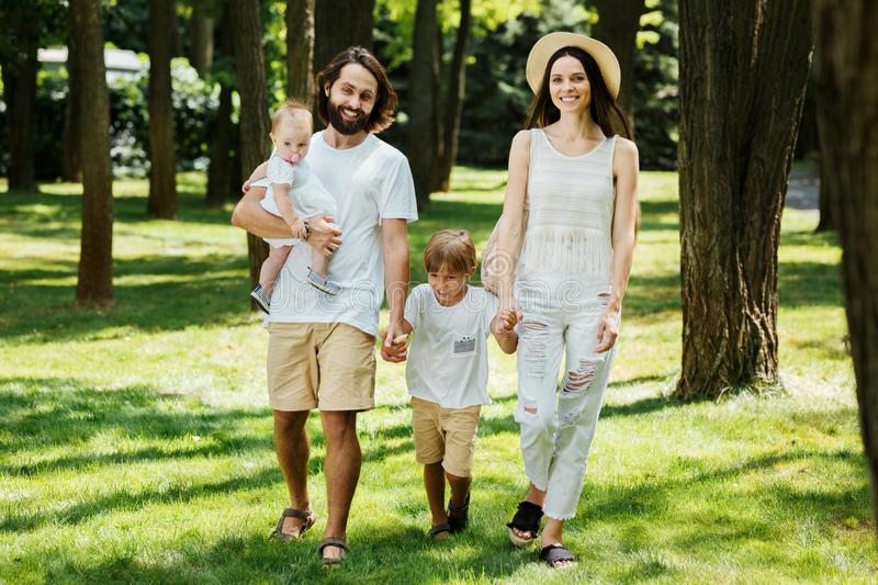 Happy young family dressed in the white casual clothes walks in the park on a sunny summer day. stock image