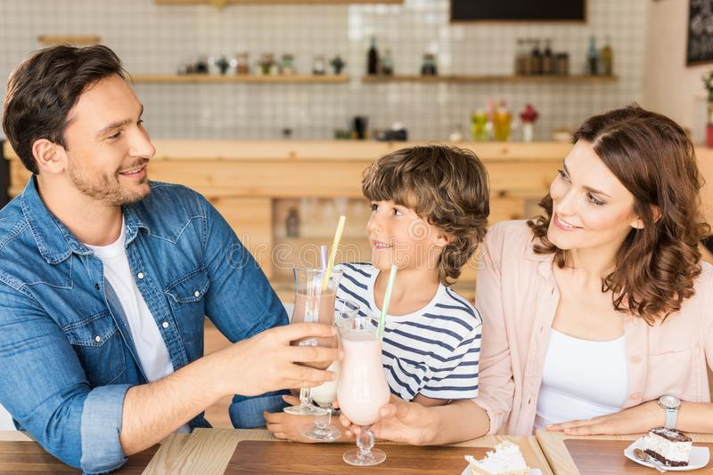 Happy young family drinking milkshakes in cafe and spending. Time together royalty free stock image