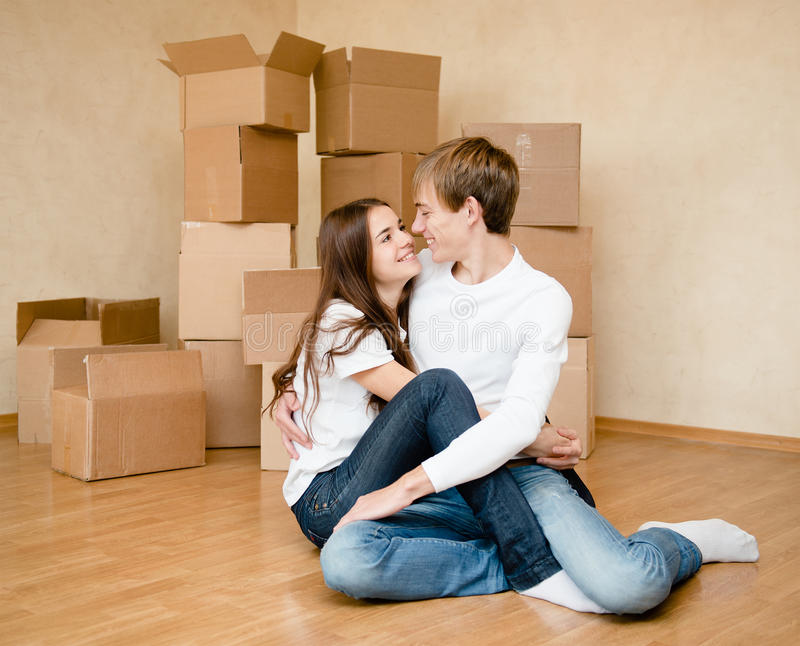Happy young family embracing on a background of cardboard royalty free stock photo