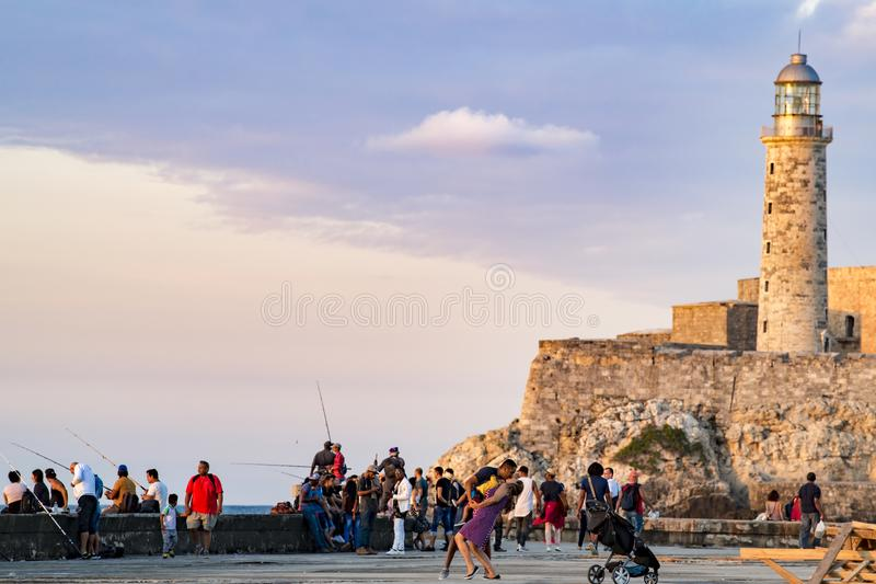 Happy young family dancing in evening sun on Malecon, Havana. Father, child and pregnant mother plus angler enjoy evening at Malecon in front of Lighthouse stock image