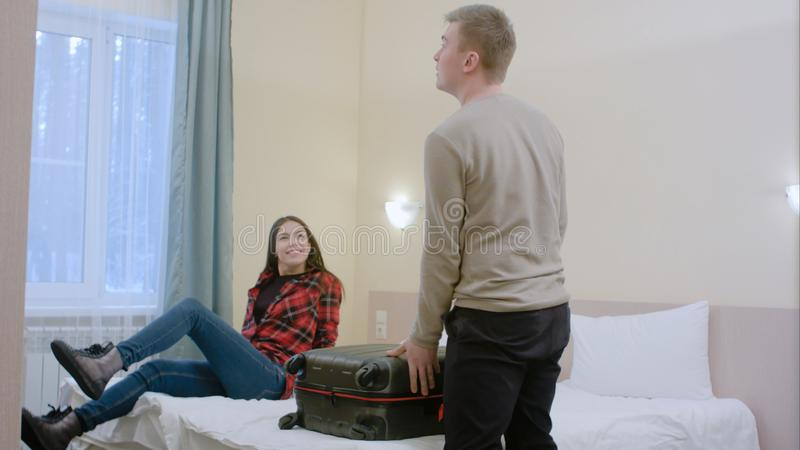Happy young family entering a hotel room and unpack luggage. Professional shot in 4K resolution. 068. You can use it e.g. in your commercial video, business stock images
