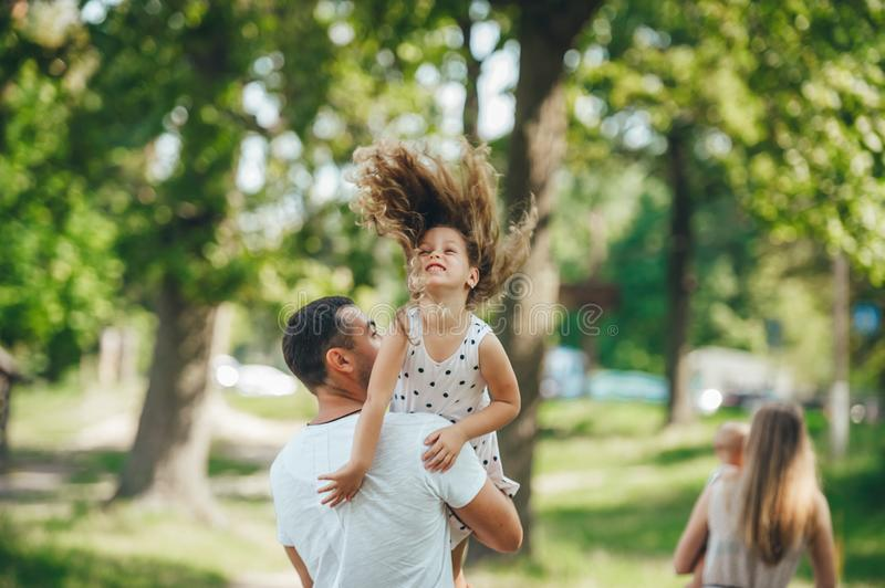 Happy young family father, mother and children having fun outdoors, playing together in summer park, countryside royalty free stock image