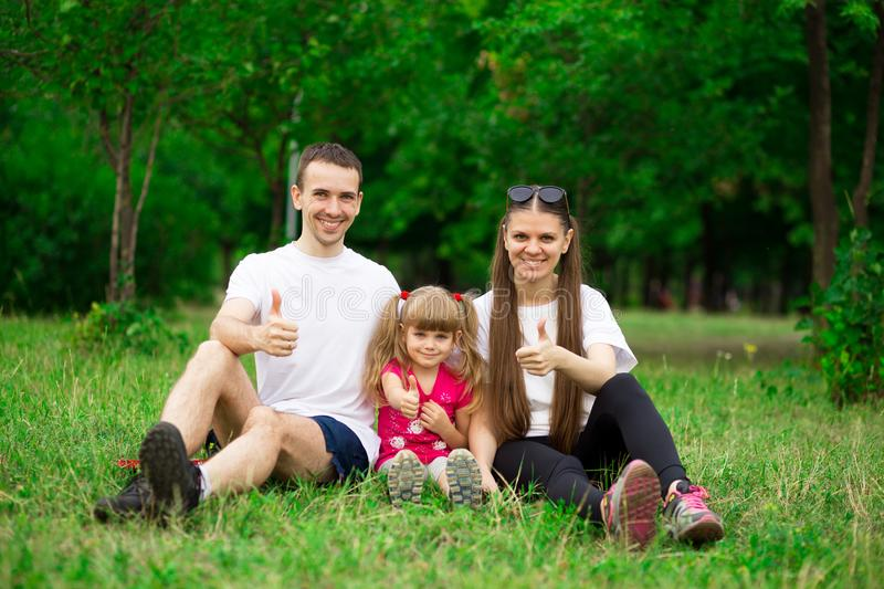 Happy young family of father, mother and little girl sit on green grass in park, enjoying walk in natural stock photo
