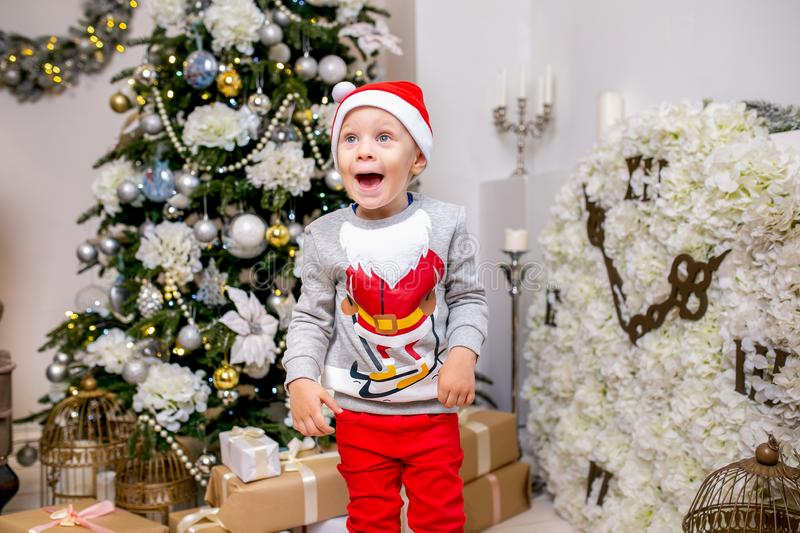 Happy young family, father, mother and son, in Christmas evening in home. A little boy in Santa`s hat stand near the tree with royalty free stock image