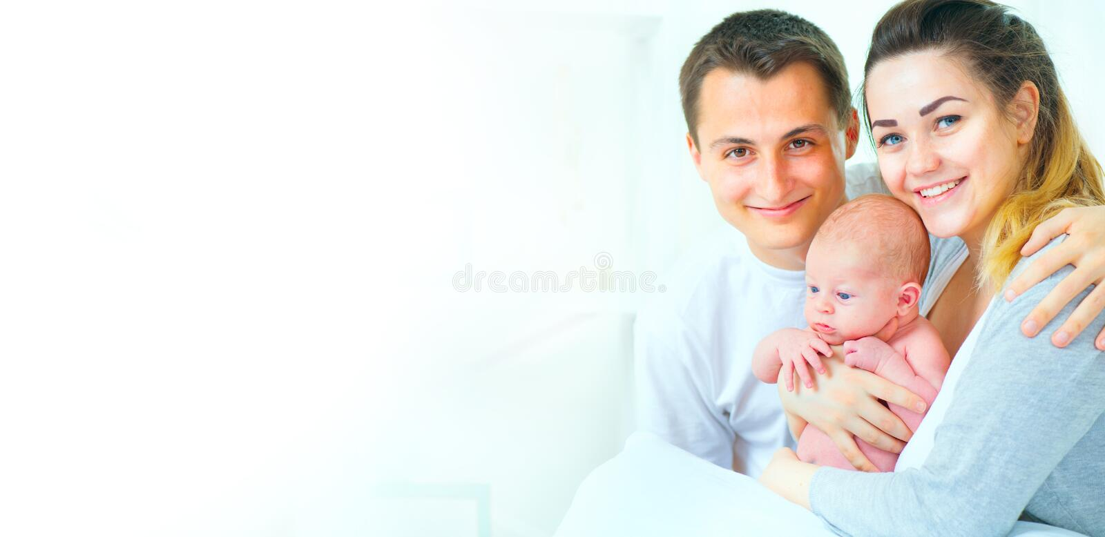 Happy young family. Father, mother and their newborn baby stock photography