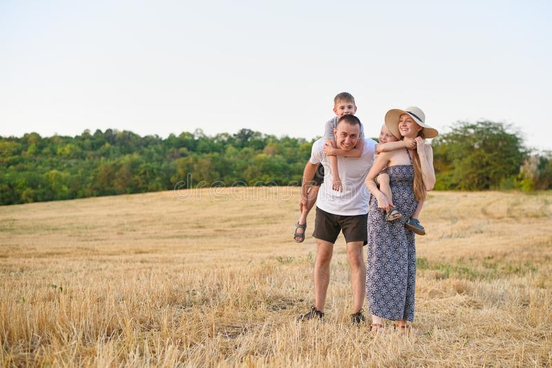 Happy young family. A father, a pregnant mother, and two little sons on their backs. Beveled wheat field on the background. Sunset. Time royalty free stock image