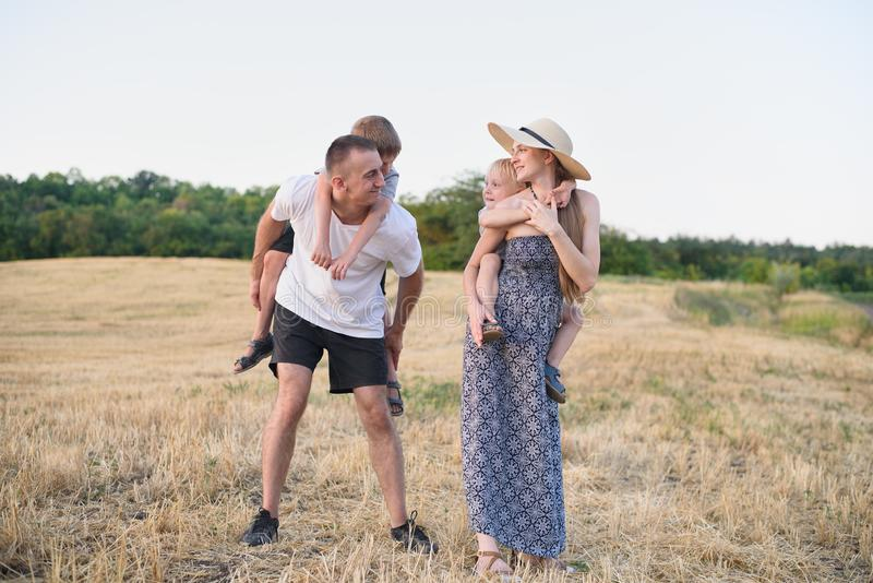 Happy young family. A father, a pregnant mother, and two little sons on their backs. Beveled wheat field on the background. Sunset. Time royalty free stock photos