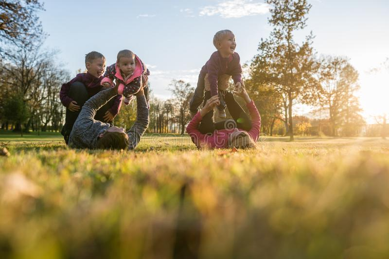 Happy young family of five playing in autumn park royalty free stock photos
