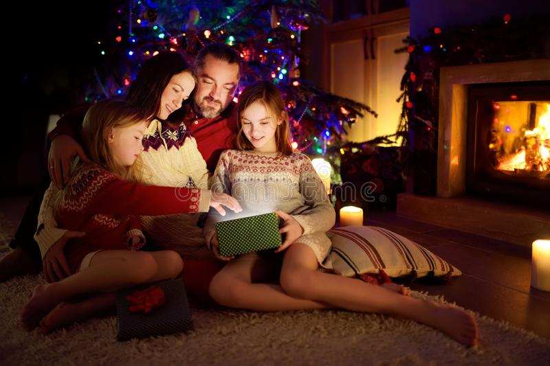 Happy young family of four using a tablet pc at home by a fireplace in warm and cozy living room on Christmas eve royalty free stock photography