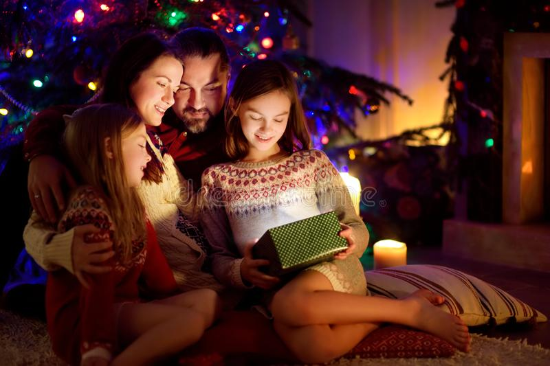 Happy young family of four using a tablet pc at home by a fireplace in warm and cozy living room on Christmas eve royalty free stock photo