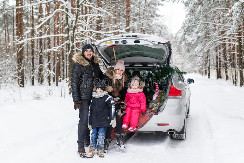 A happy young family getting ready for the Christmas morning, standing in the back of the car in forest stock image