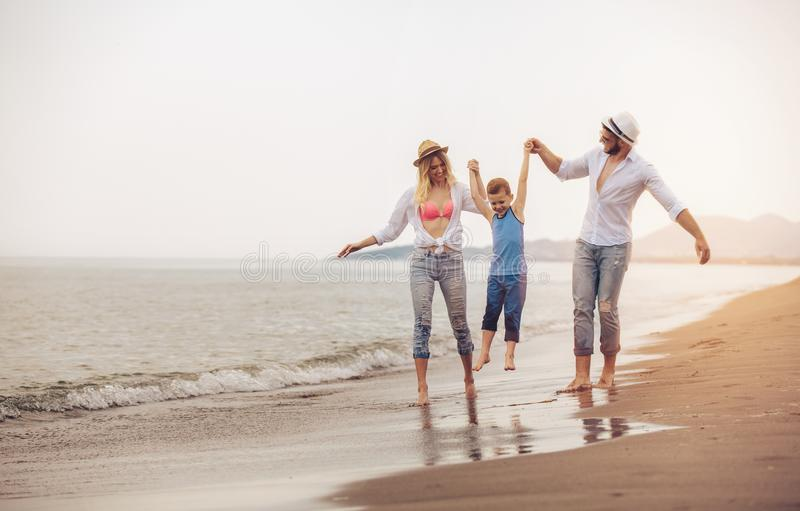 Young family have fun on beach run and jump stock images