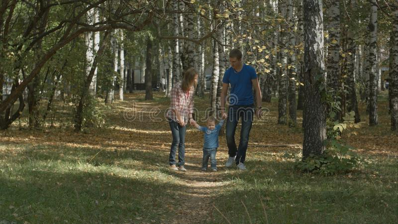 Happy young family is having fun in the autumn park outdoors on a sunny day. Mother, father swing their little baby-boy. royalty free stock photography