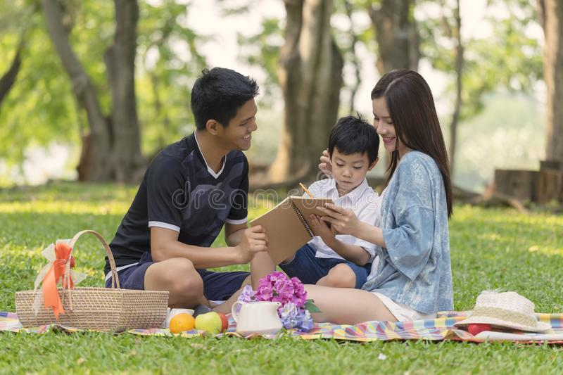 Happy young family having fun outside and sitting picnic in the park stock images