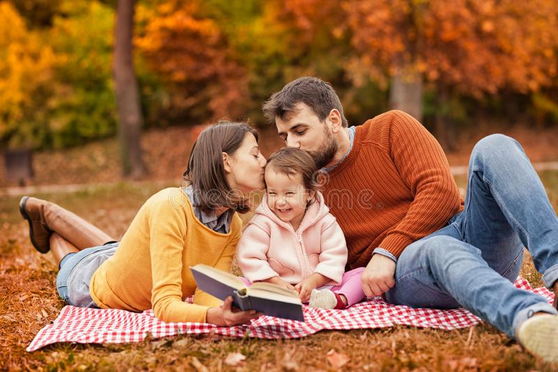 Happy young family having fun on picnic blanket stock photography