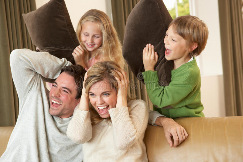 Happy young family having fun with pillows on sofa. Smiling stock photo