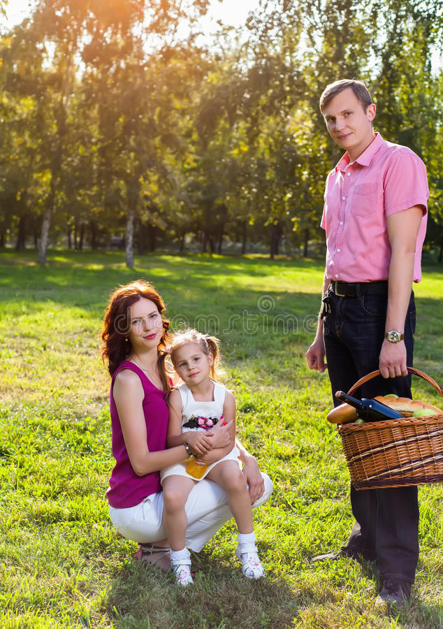 Happy young family having picnic at meadow royalty free stock photos