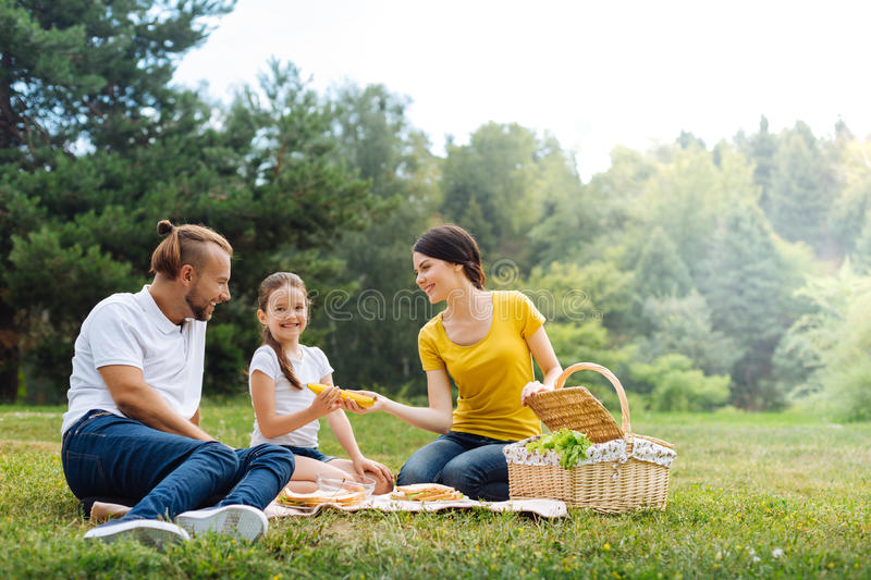 Happy young family having a picnic in the park. Relaxing weekend. Beautiful young mother giving her daughter a banana while the entire family enjoying picnic in stock photography
