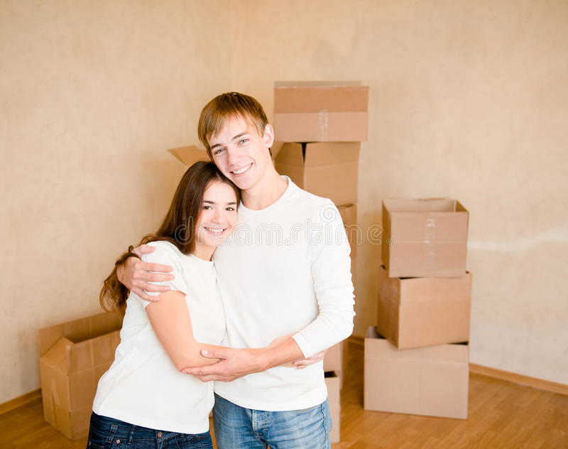 Happy young family hugging on a background of cardboard boxes stock photos