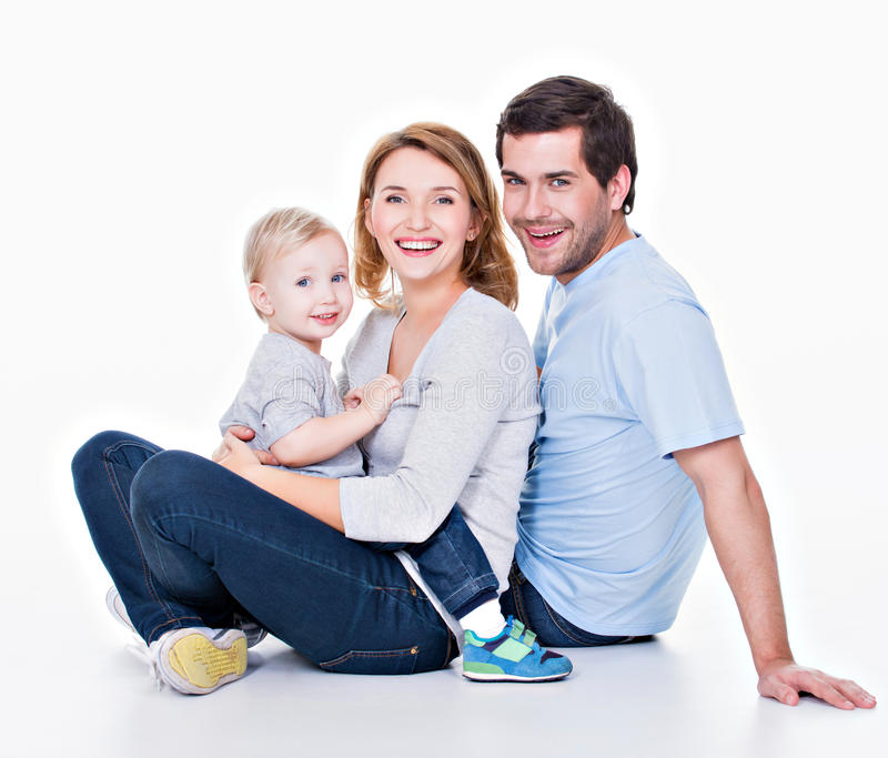 Happy young family with little child. Photo of the happy young family with little child sitting on the floor - isolated on white background royalty free stock photos