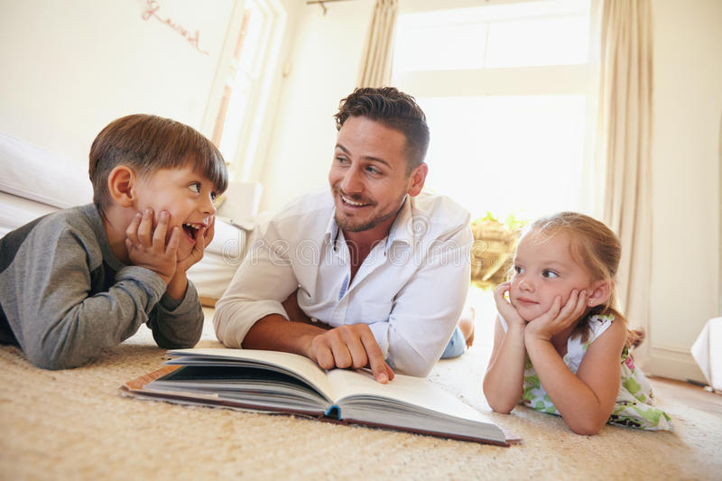 Happy young family lying on the floor reading a book stock image