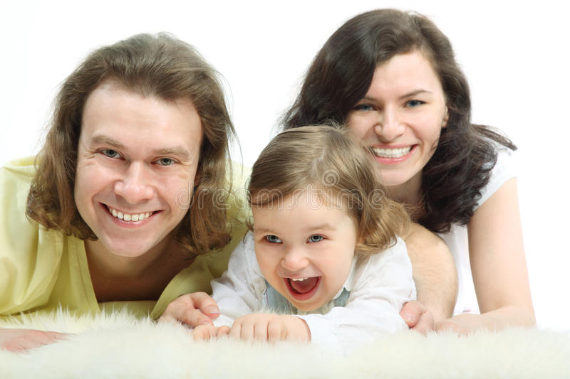 Happy young family are lying on fur royalty free stock photography