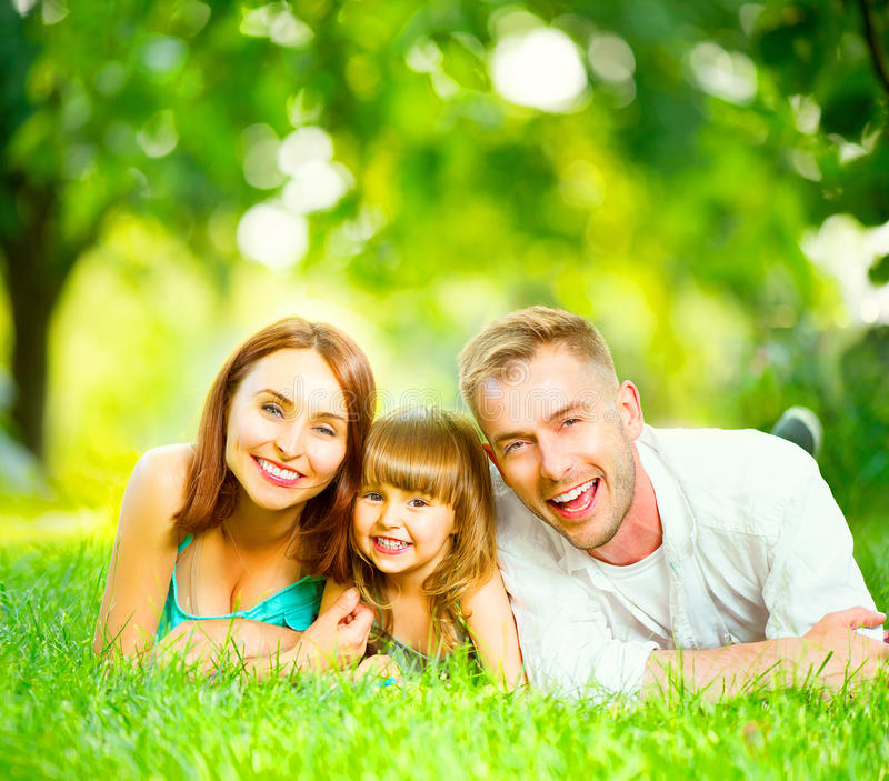 Happy young family lying on green grass. Happy joyful young family lying on green grass stock photos
