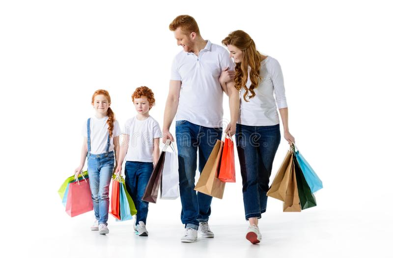 Happy young family with paper bags walking together. Isolated on white stock photos