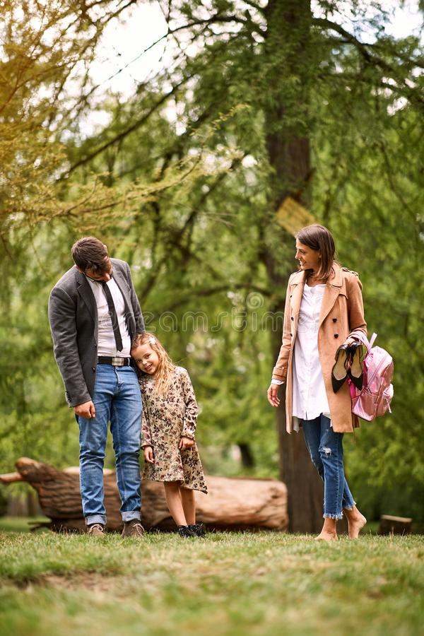 Happy family in park after school and business work royalty free stock photos