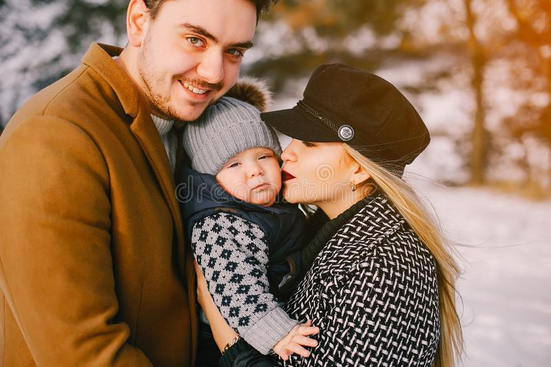 Happy family in the park. Happy young family in the park on a snowy winter day stock image