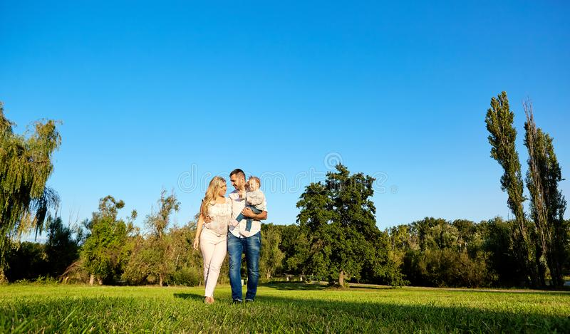 Happy young family in the park on a sunny day. royalty free stock photography