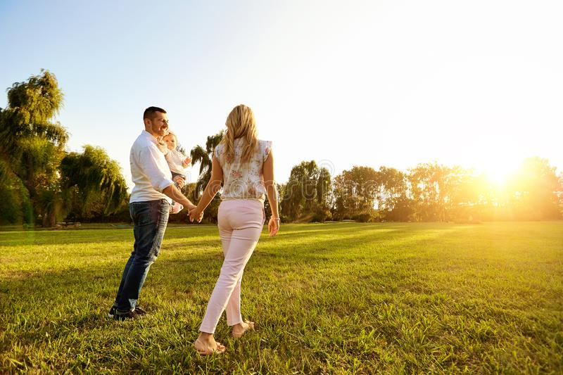 Happy young family in the park at sunset. royalty free stock photo