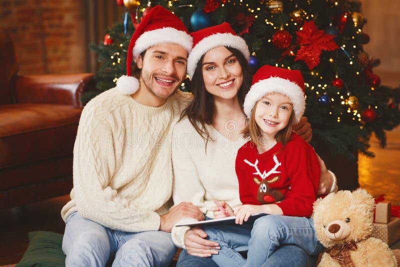 Happy young family posing over beautiful xmas tree royalty free stock image