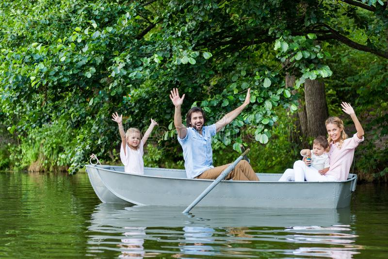 Happy young family with raised hands riding boat on lake. At park royalty free stock image