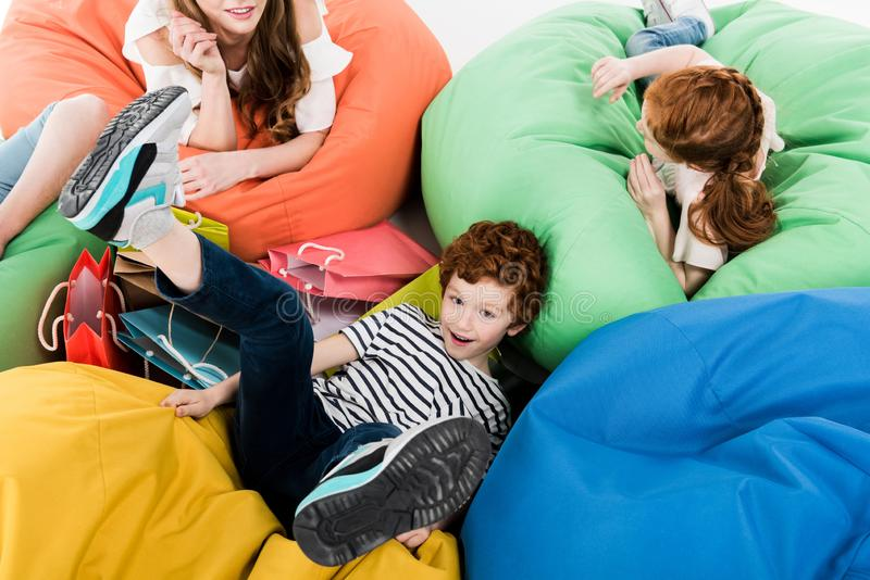 Happy young family resting on bean bag chairs after shopping. On white royalty free stock images