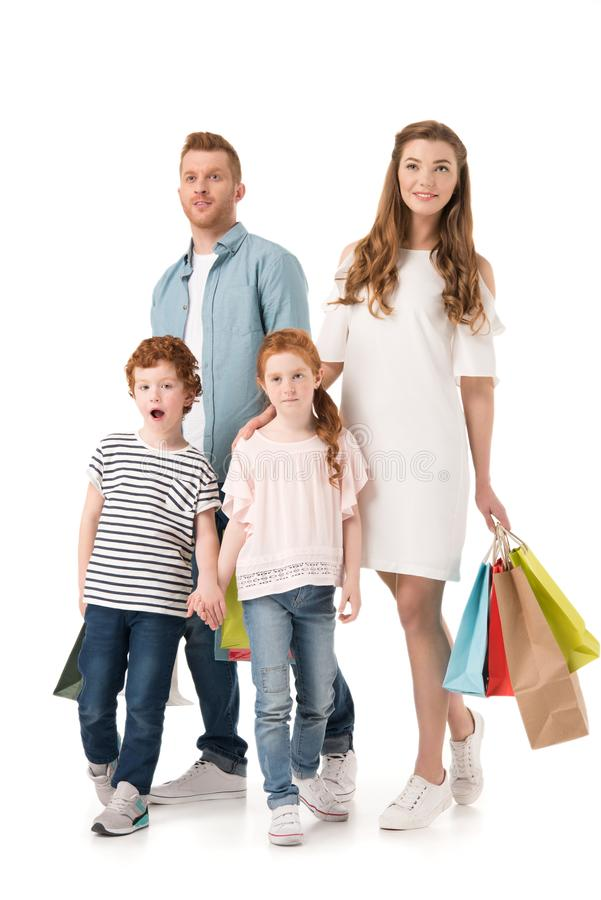 Happy young family with shopping bags standing together. Isolated on white royalty free stock images