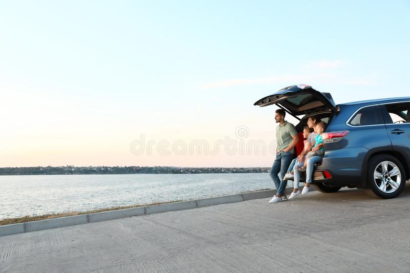 Happy young family sitting in car trunk stock photo