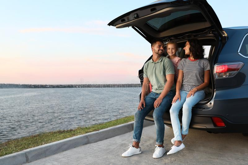 Happy young family sitting in car trunk stock photos