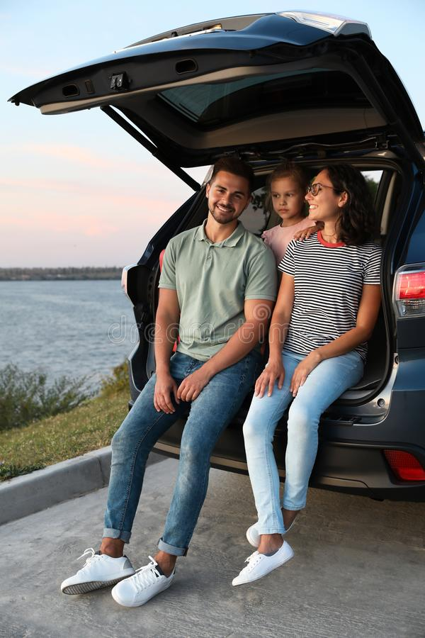 Young family sitting in car trunk on riverside stock photography