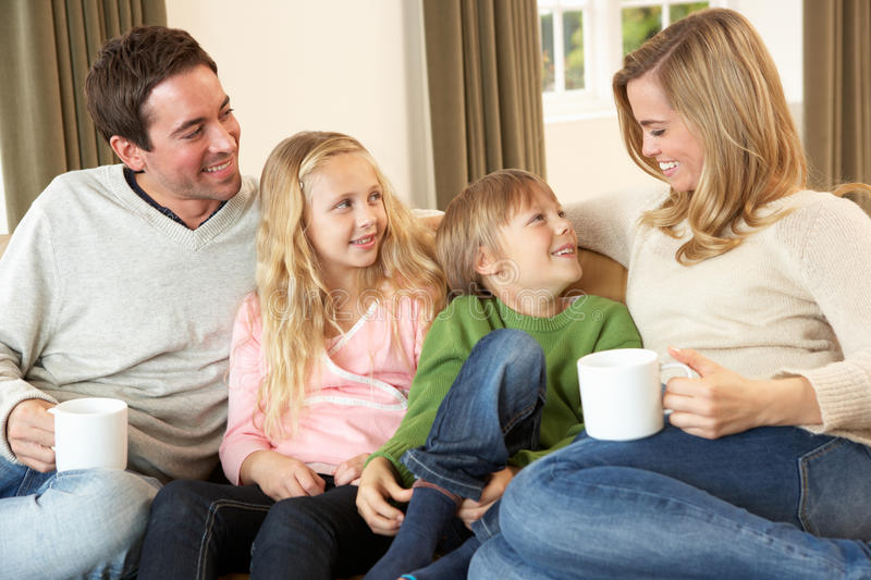 Happy young family sitting and talking on sofa stock photography