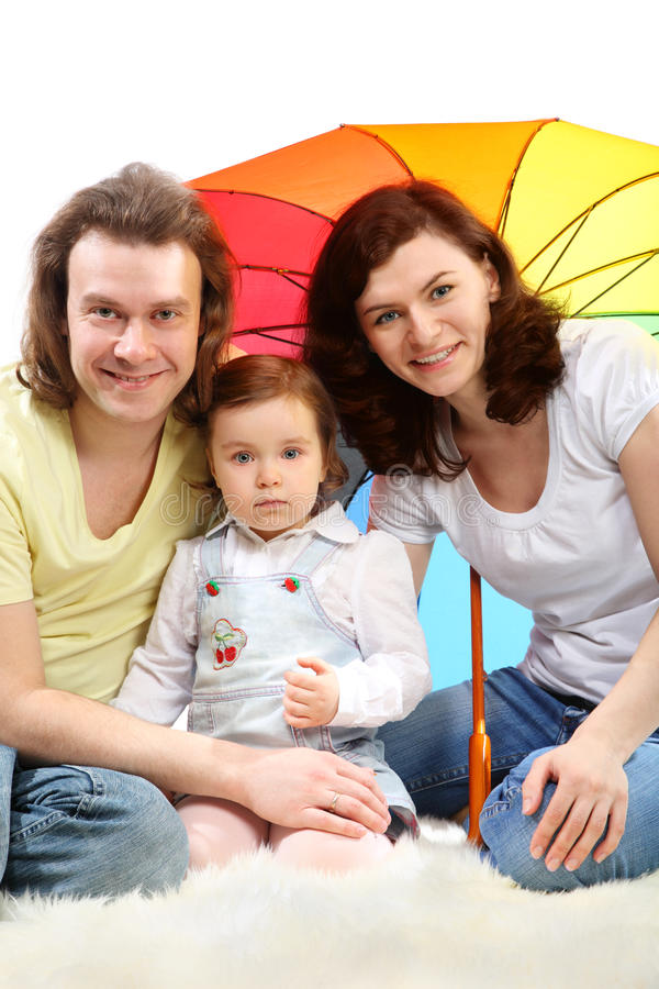 Happy young family are sitting under umbrella. Happy young family - mother, father and little daughter - are sitting under colored umbrella on a white fluffy fur royalty free stock photos