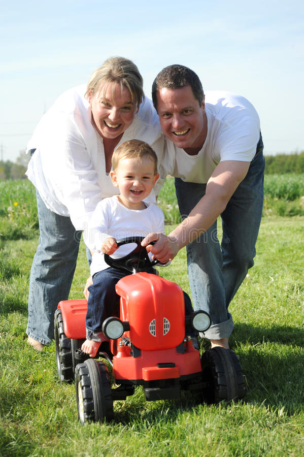Happy young family with small child. Young family with a 2 years young toddler driving his red tractor stock images