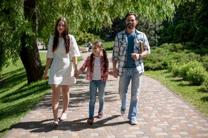 Happy young family spending time in park on summer day royalty free stock photography