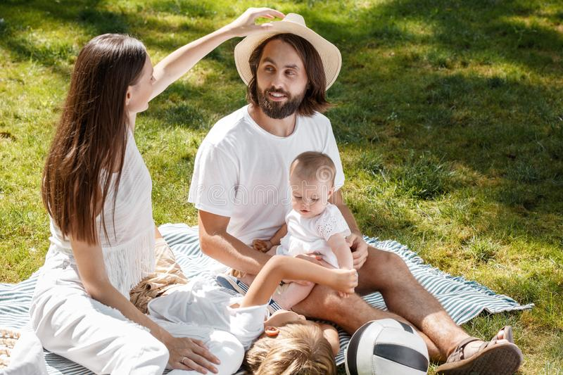 Happy young family on a sunny summer picnic. They are wearing white clothes and sitting with kids on the striped royalty free stock images