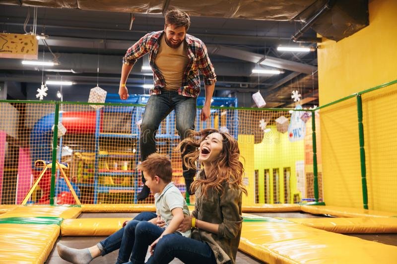 Happy young family with their little son jumping. On a trampoline together at the entertainment centre stock images